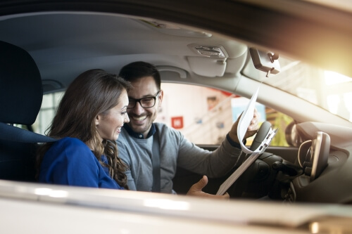 A smiling girl holding car key